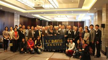 Group of Aggies holding up UC Davis flag
