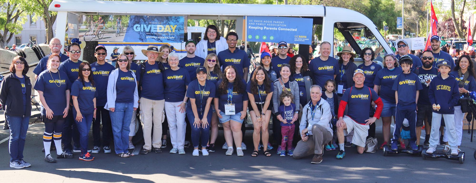 UC Davis alumni standing in front of a vehicle at the Picnic Day Parade
