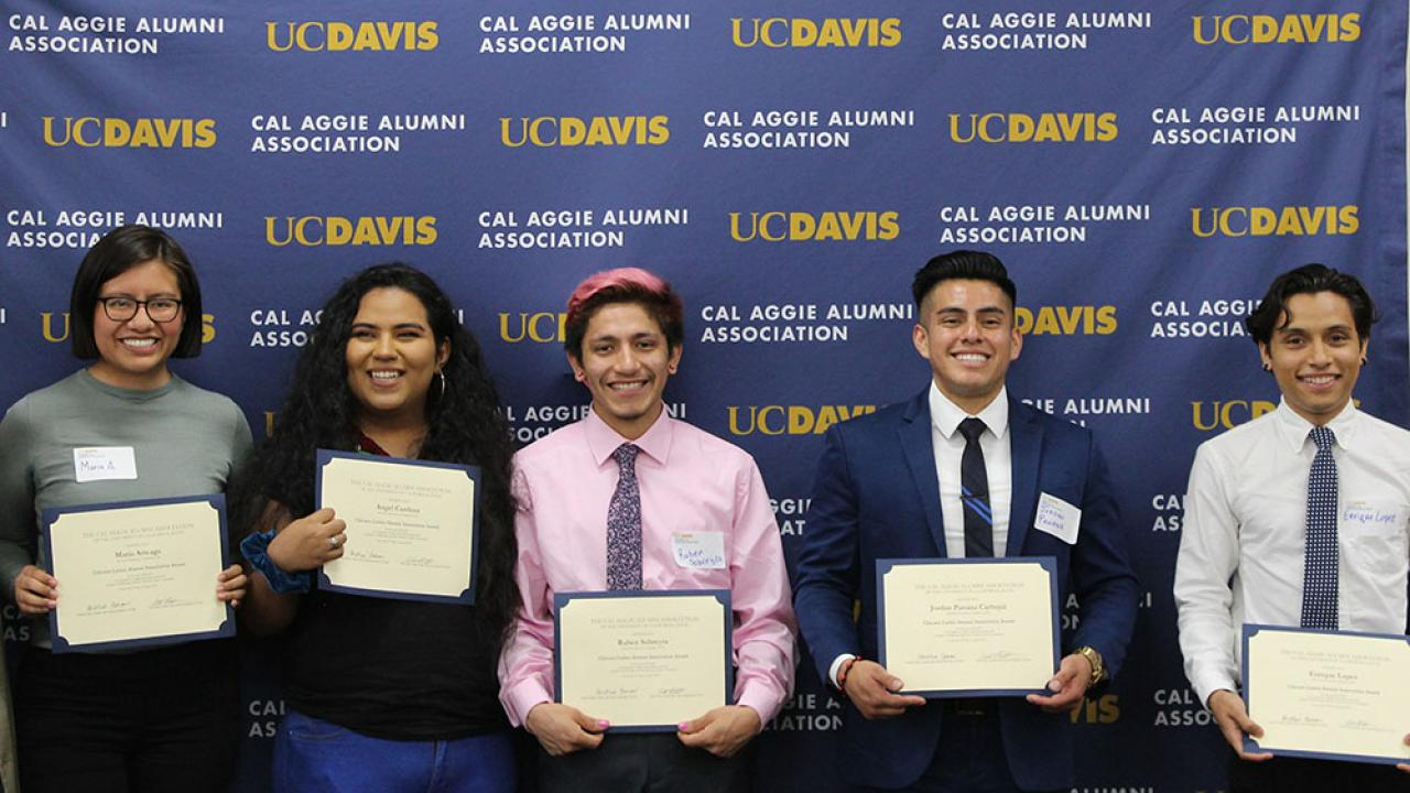Five people standing in a row, facing camera and holding certificates