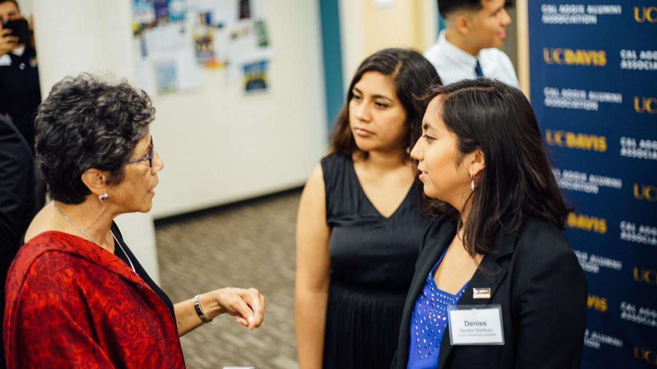 UC Davis students interacting with an alumna at a career fair
