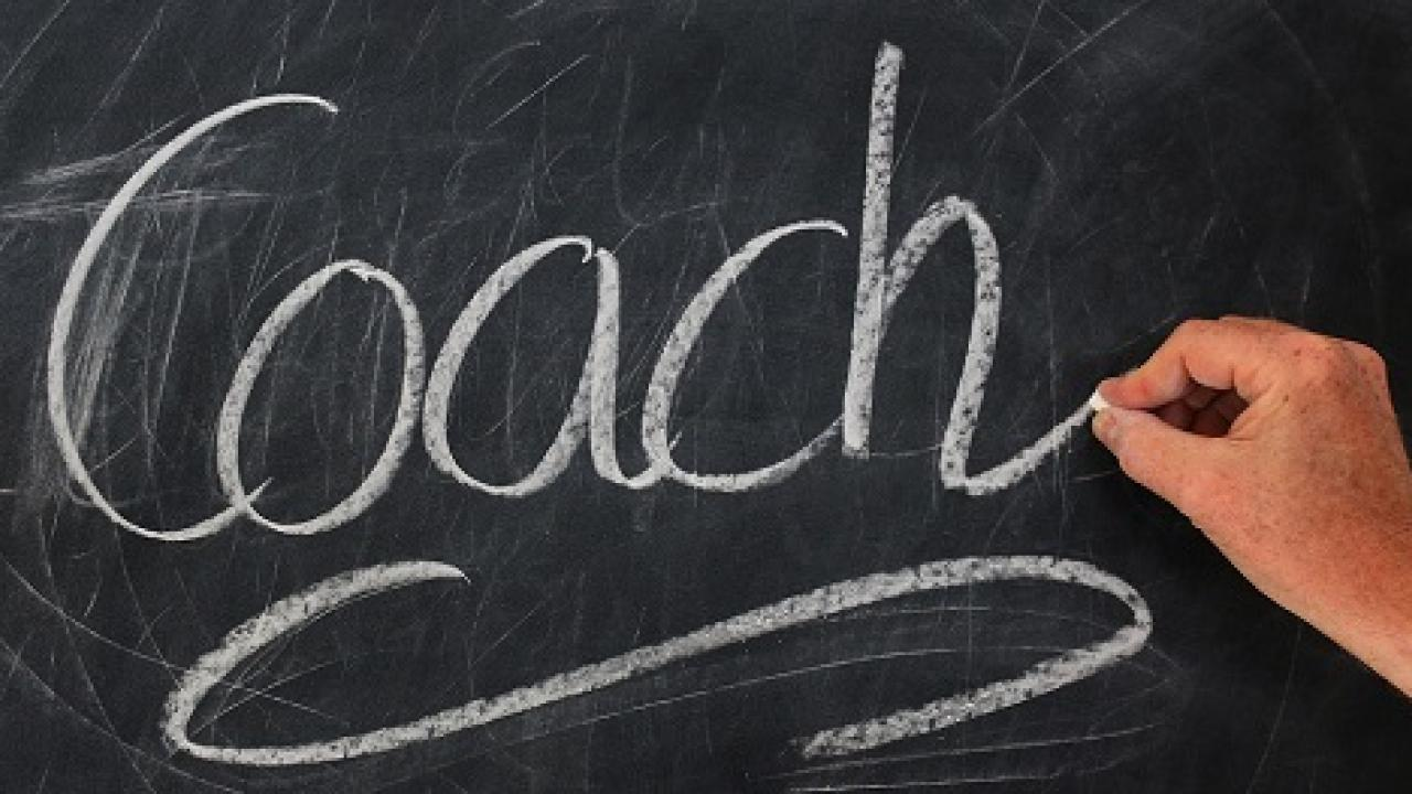 Hand writing coach in chalk on a chalkboard