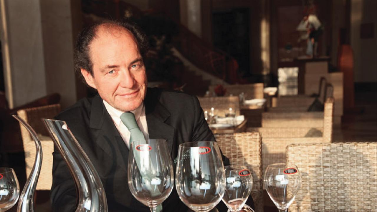 Georg Riedel with wine glasses at a table