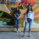 Picture of Aggie House Co-founders Ashley Lo (right) and Alan O'Brien. Both are standing in front of a colorful mural.