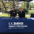 Two people sitting at a table with a sign that says UC Davis Parents Program