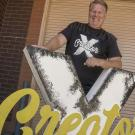 Shawn Sullivan standing with a Creator X sign